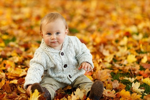 baby in sweater sitting on autumn leaves