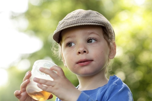 toddler with hat drinking juice