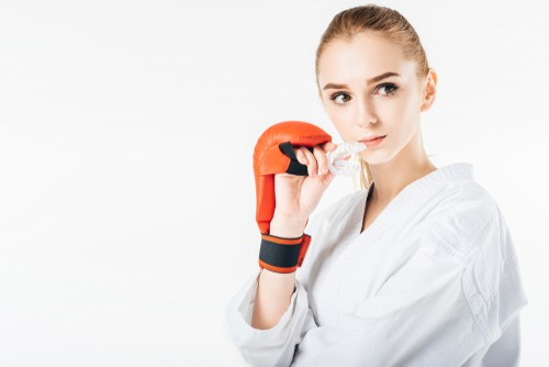 girl boxer holding sports mouthguard