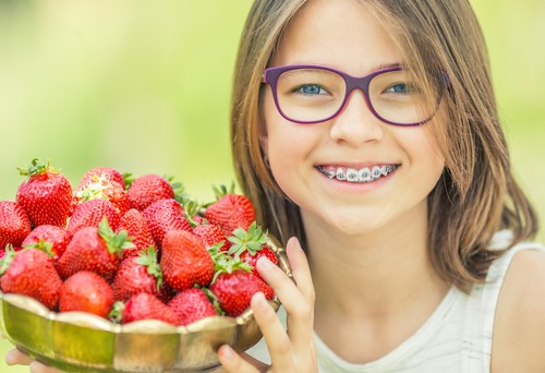girl with braces holding strawberries