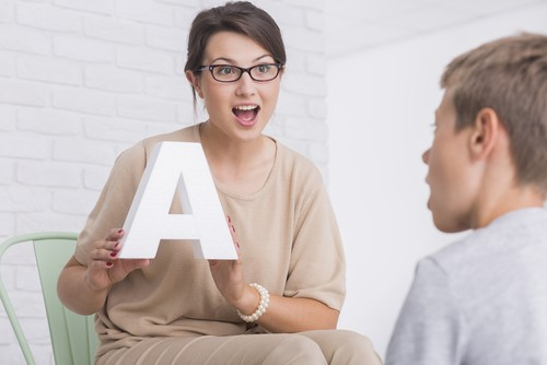 woman holding up letter lauguage tutor